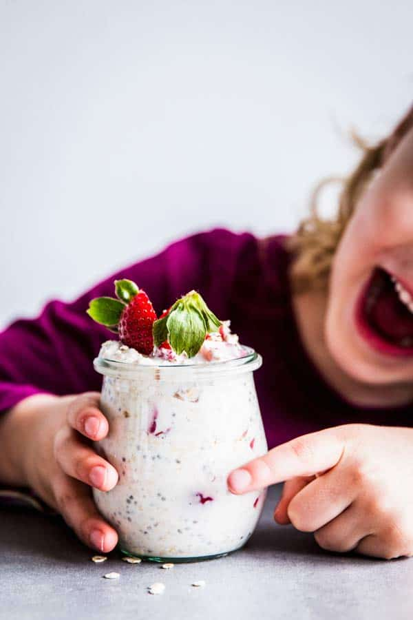 Girl with strawberry overnight oats in a jar.