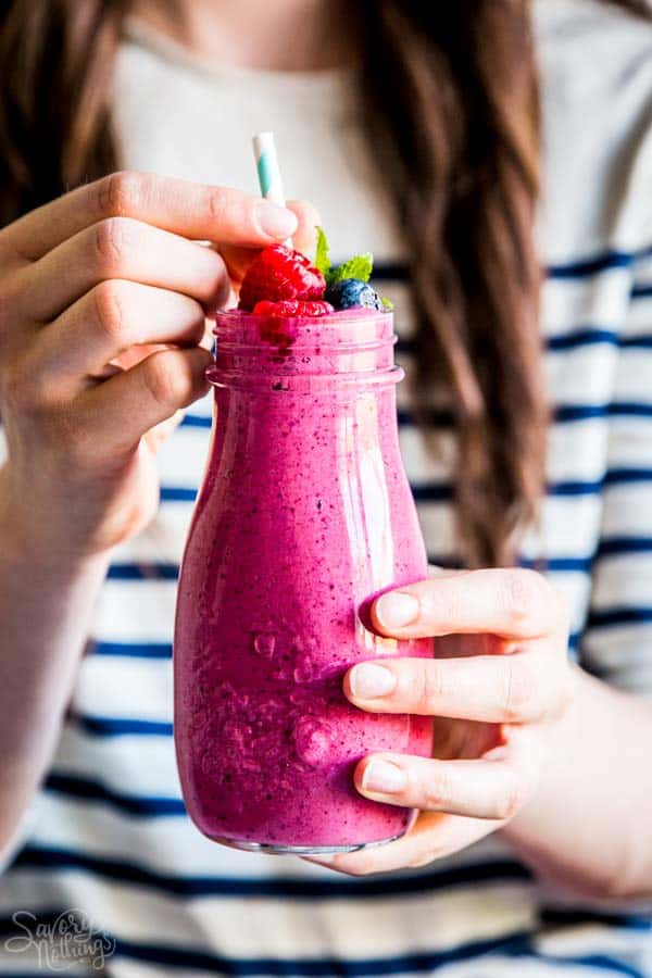 woman holding a bottle of berry smoothie