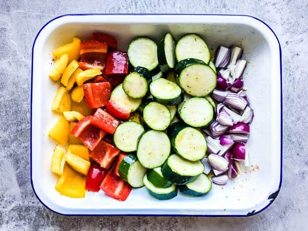 sliced vegetables marinating in a white dish for greek chicken kabobs