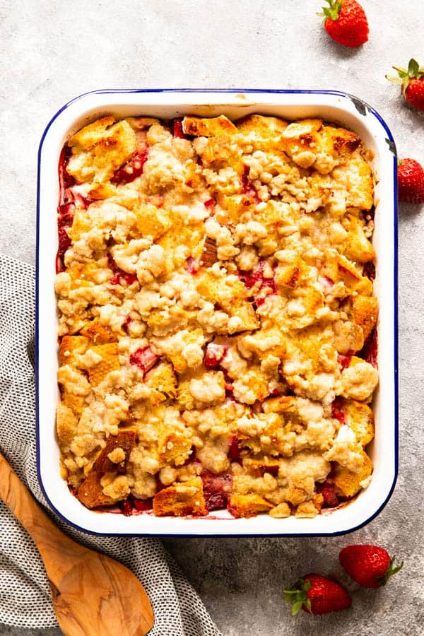enamel casserole dish with French toast bake surrounded by fresh strawberries