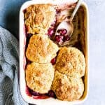 fresh cherry cobbler in a casserole dish with a spoon