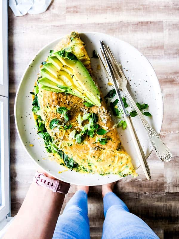 woman holding an omelet on a white plate