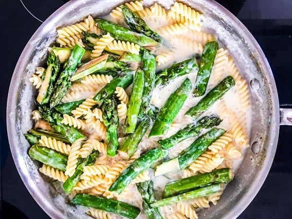 pasta and asparagus in a skillet in creamy sauce