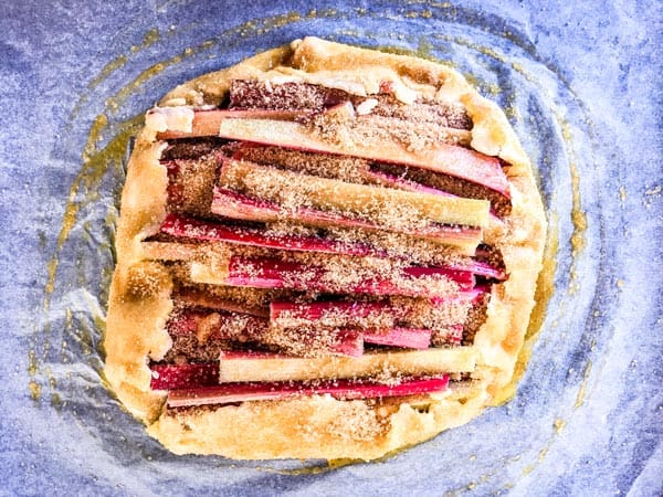 unbaked rhubarb galette sprinkled with brown sugar