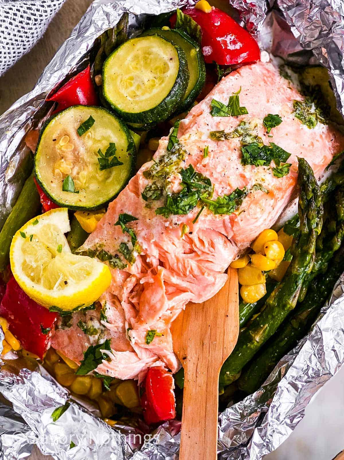 close up photo of flaked salmon in foil pouch with summer vegetables and wooden fork