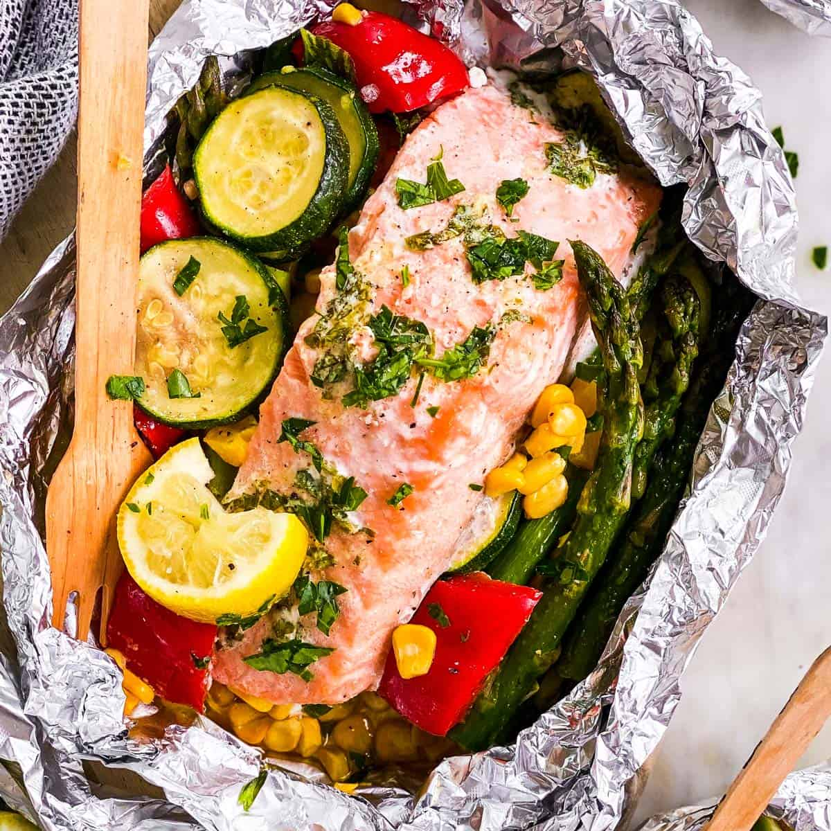 overhead view of salmon fillet in opened foil packet over bed of summer vegetables, with wooden fork stuck in vegetables