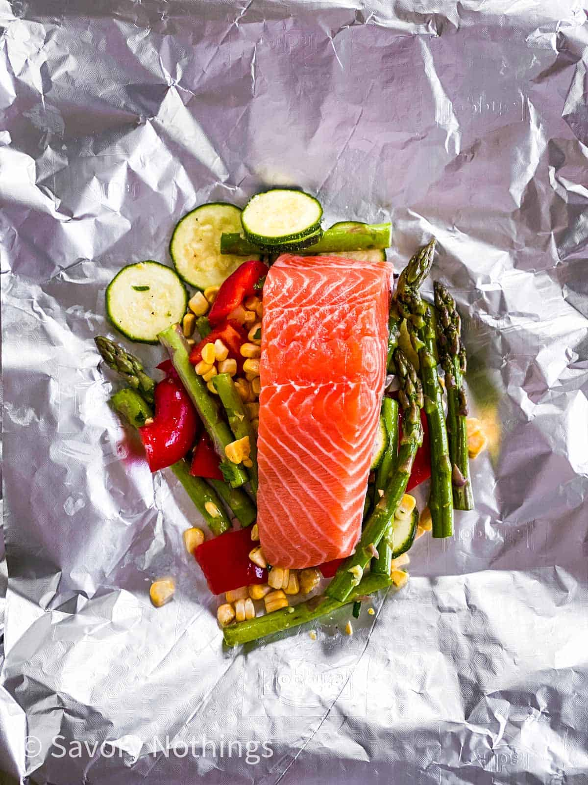 vegetables and raw salmon fillet on piece of aluminium foil