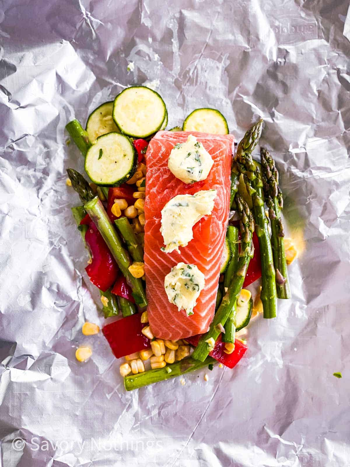 vegetables and raw salmon fillet on piece of aluminium foil topped with garlic herb butter