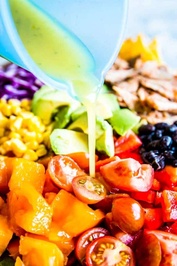 pouring dressing on chicken taco salad