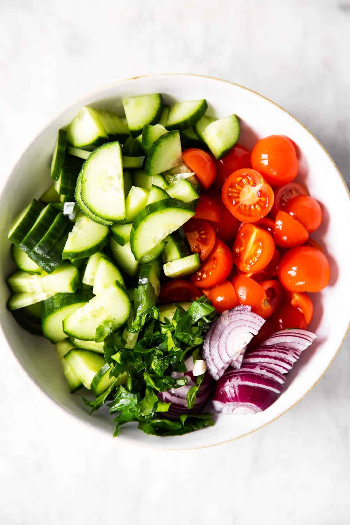 vegetables for tomato cucumber salad in white bowl