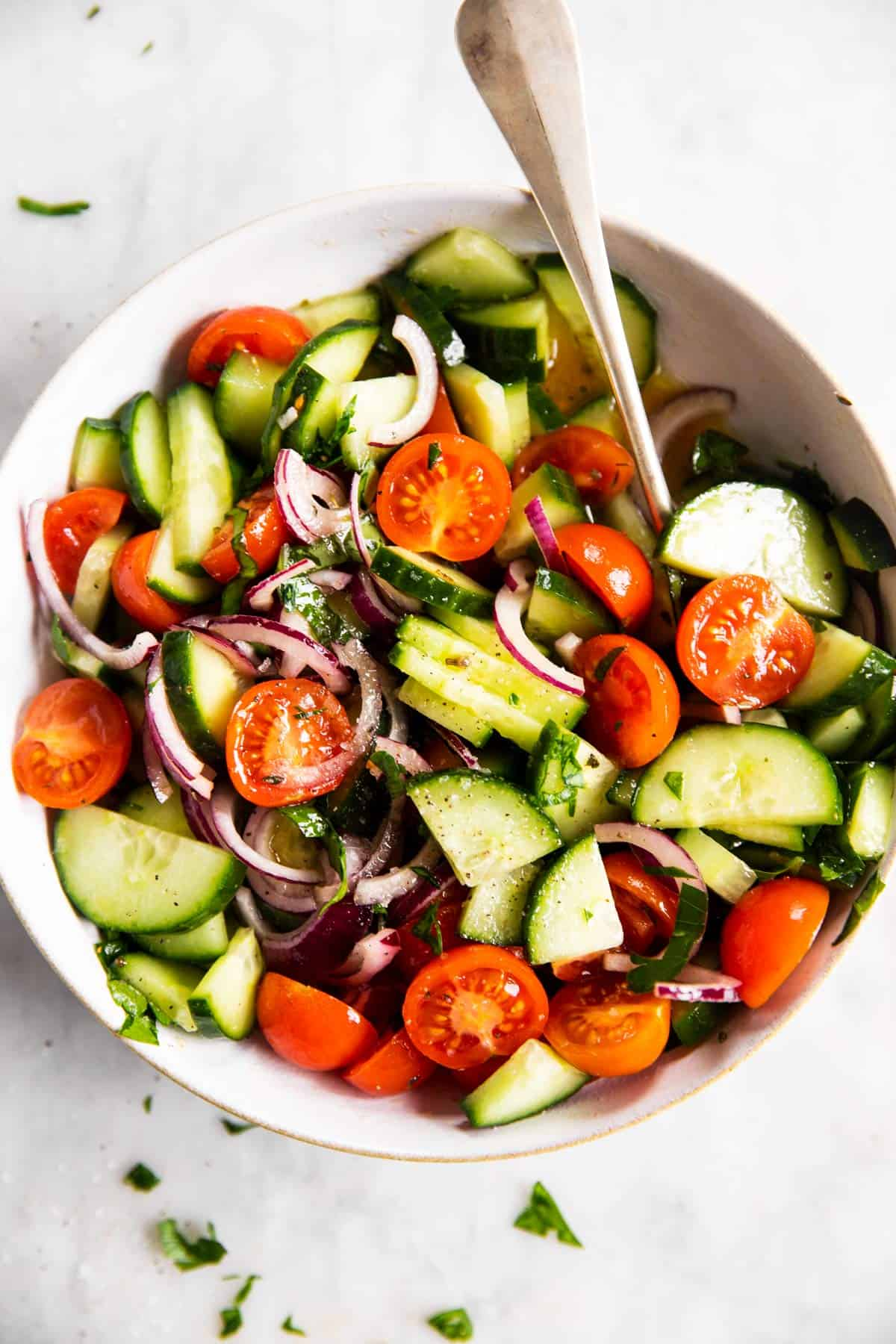 white bowl with tomato cucumber salad on marble surface