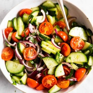 overhead view of white bowl with cucumber tomato salad