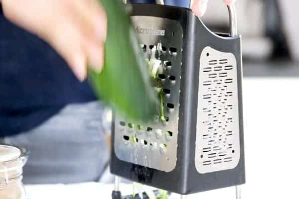 shredding zucchini on a box grater