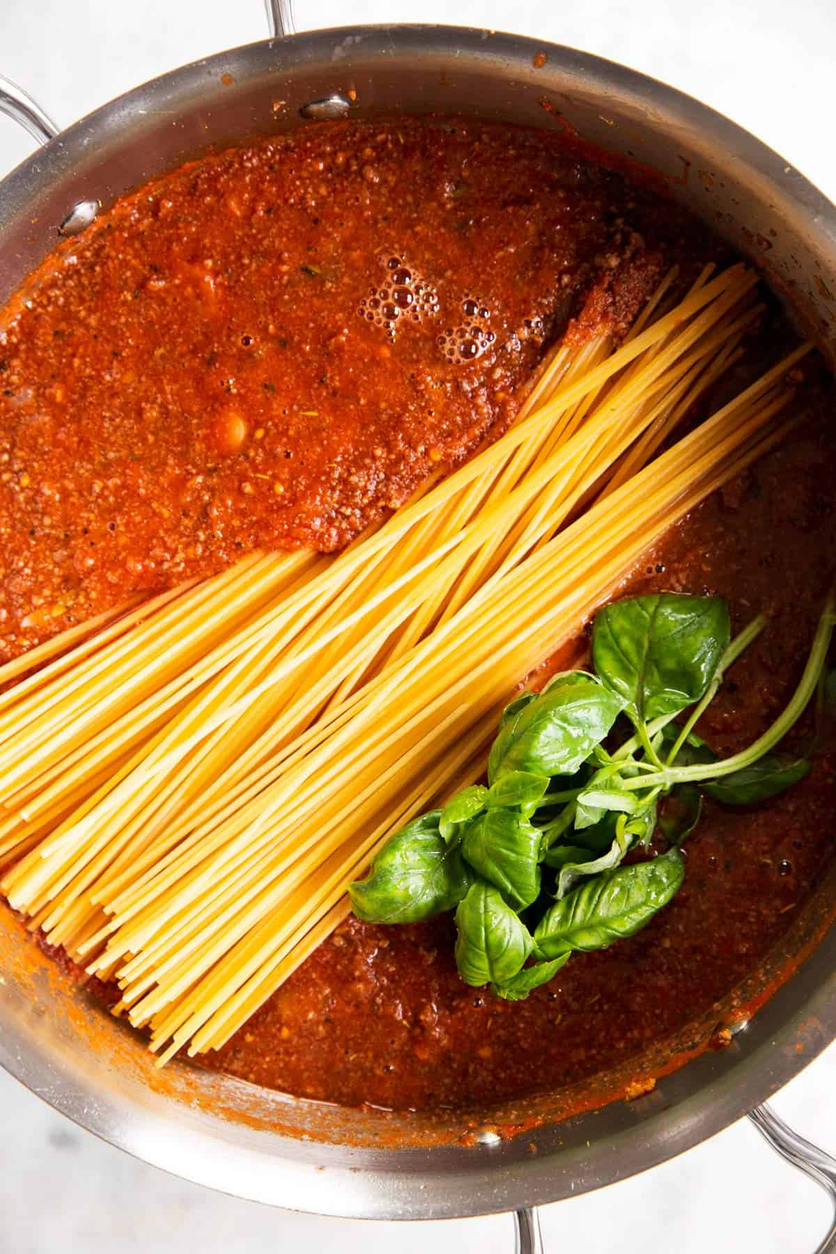 overhead view of raw spaghetti in meat sauce with basil in skillet