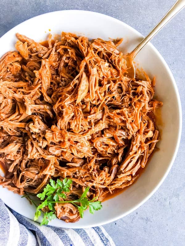 close up photo of crockpot pineapple bbq pulled pork in a serving dish