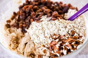 raisins, pecans and rolled oats on top of cookie dough in a glass bowl, with a purple spatula sticking out