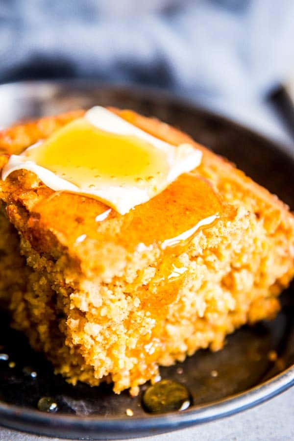 cornbread with honey and butter on a black plate