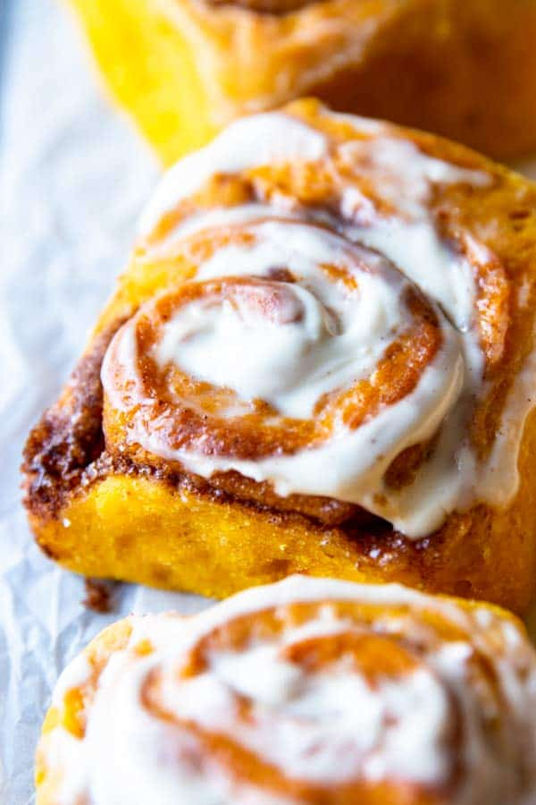 close up photo of a frosted pumpkin cinnamon roll