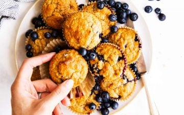 top down view on plate with oatmeal muffins, female hand grabbing one