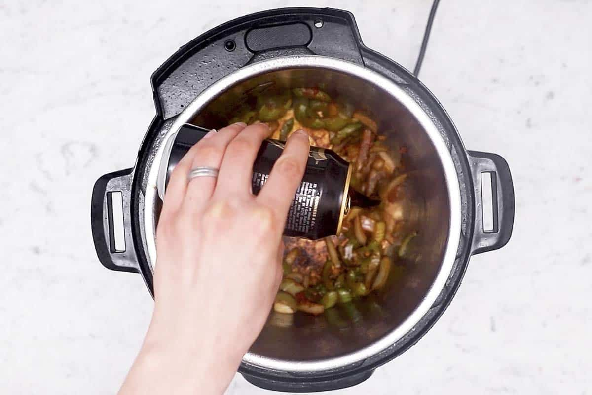 female hand pouring beer into instant pot