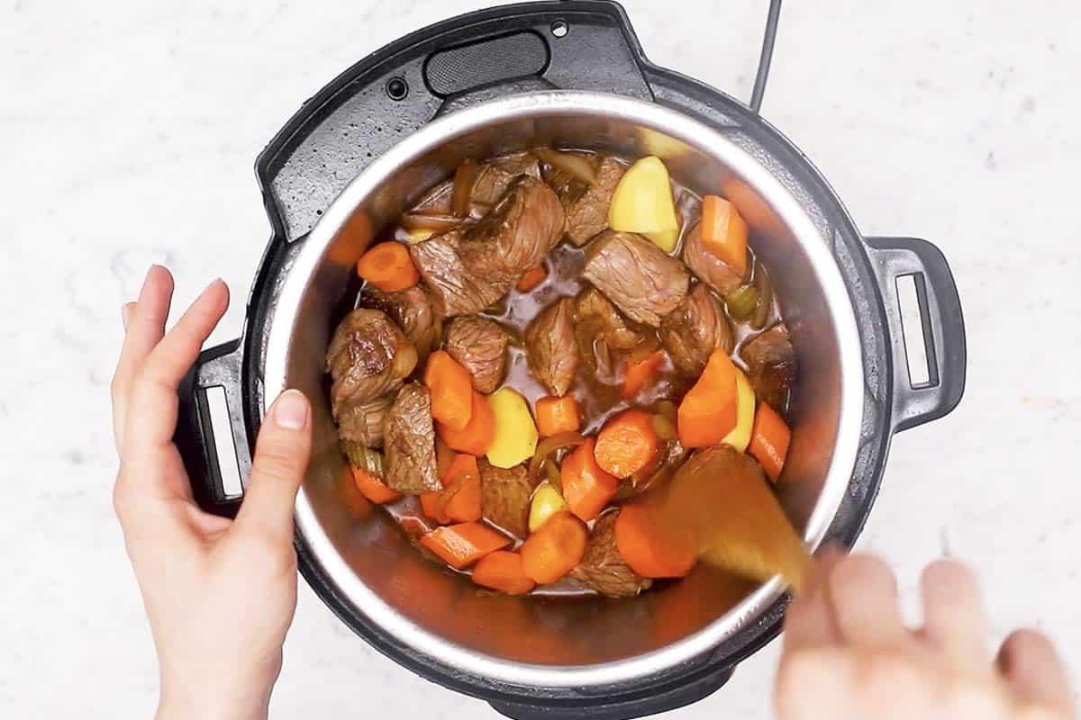 female hand stirring irish stew in instant pot