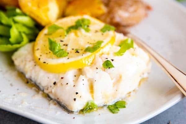 piece of garlic butter lemon baked cod fillet on a plate