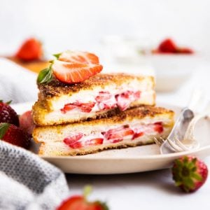 stack of stuffed French toast on a plate with fresh strawberries