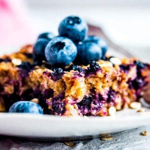 slice of blueberry baked oatmeal on a plate with fresh blueberries