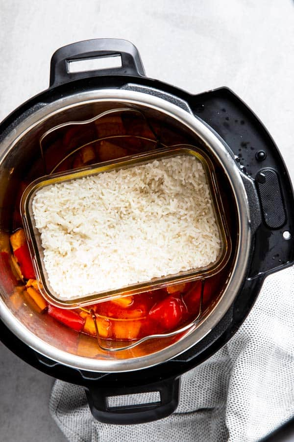 instant pot with pineapple chicken and a dish of rice inside