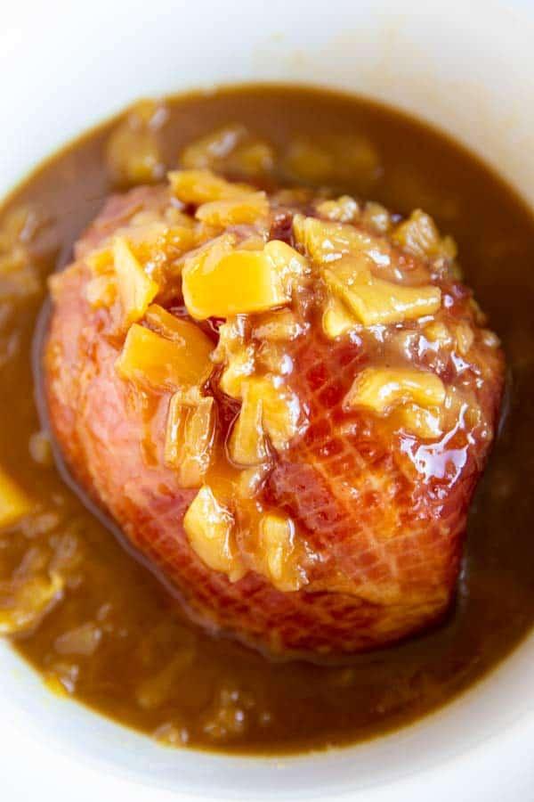 pineapple glazed ham in a white crockpot