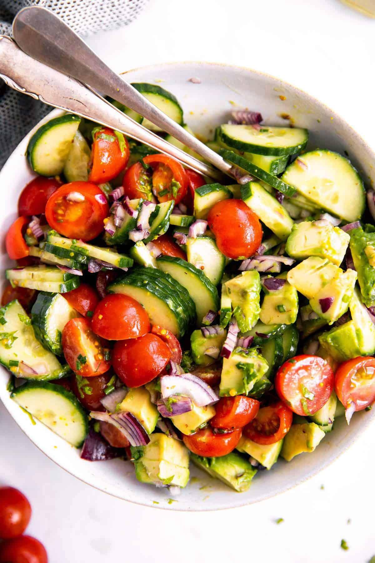 white bowl with tomato cucumber avocado salad