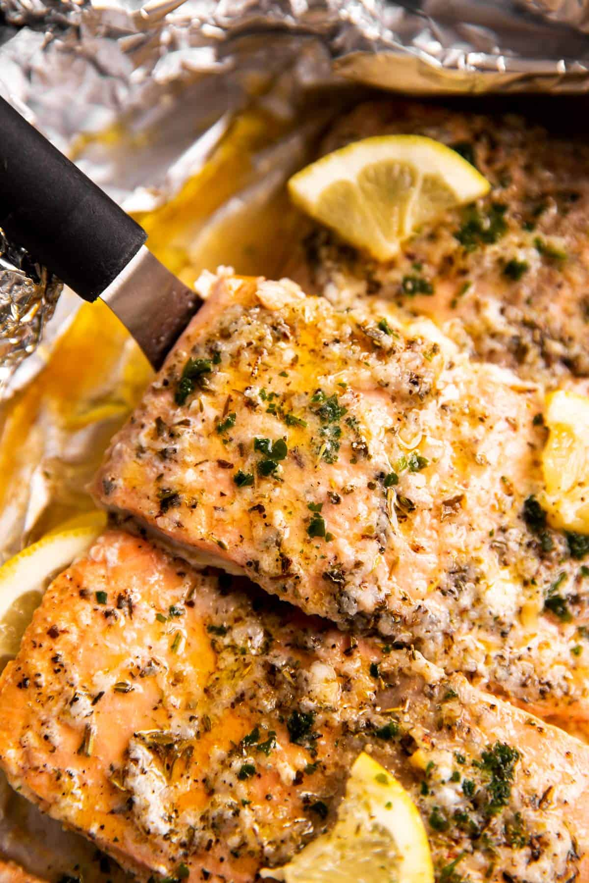 close up photo of baked salmon on lined pan