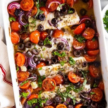 overhead view of white casserole dish filled with mediterranean baked cod