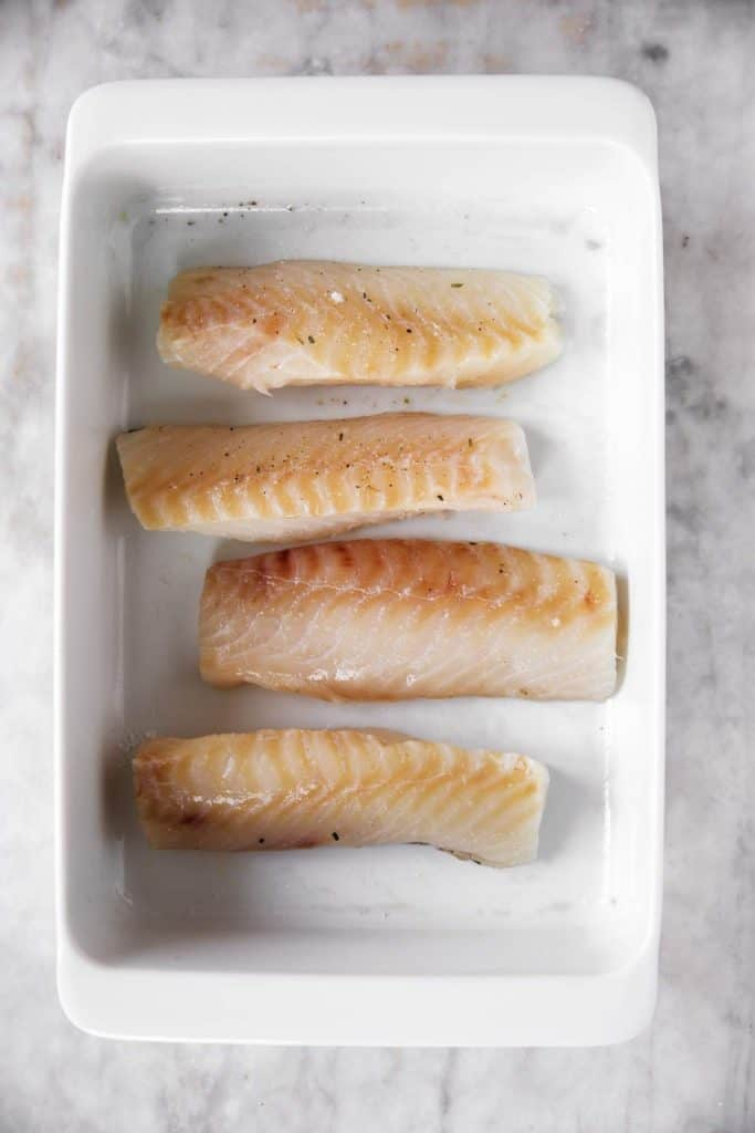 four cod fillets in white casserole dish