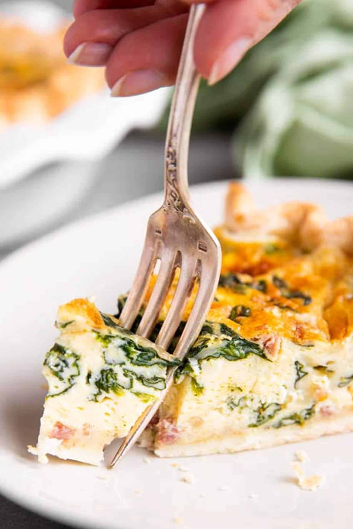 fork stuck in slice of spinach bacon quiche