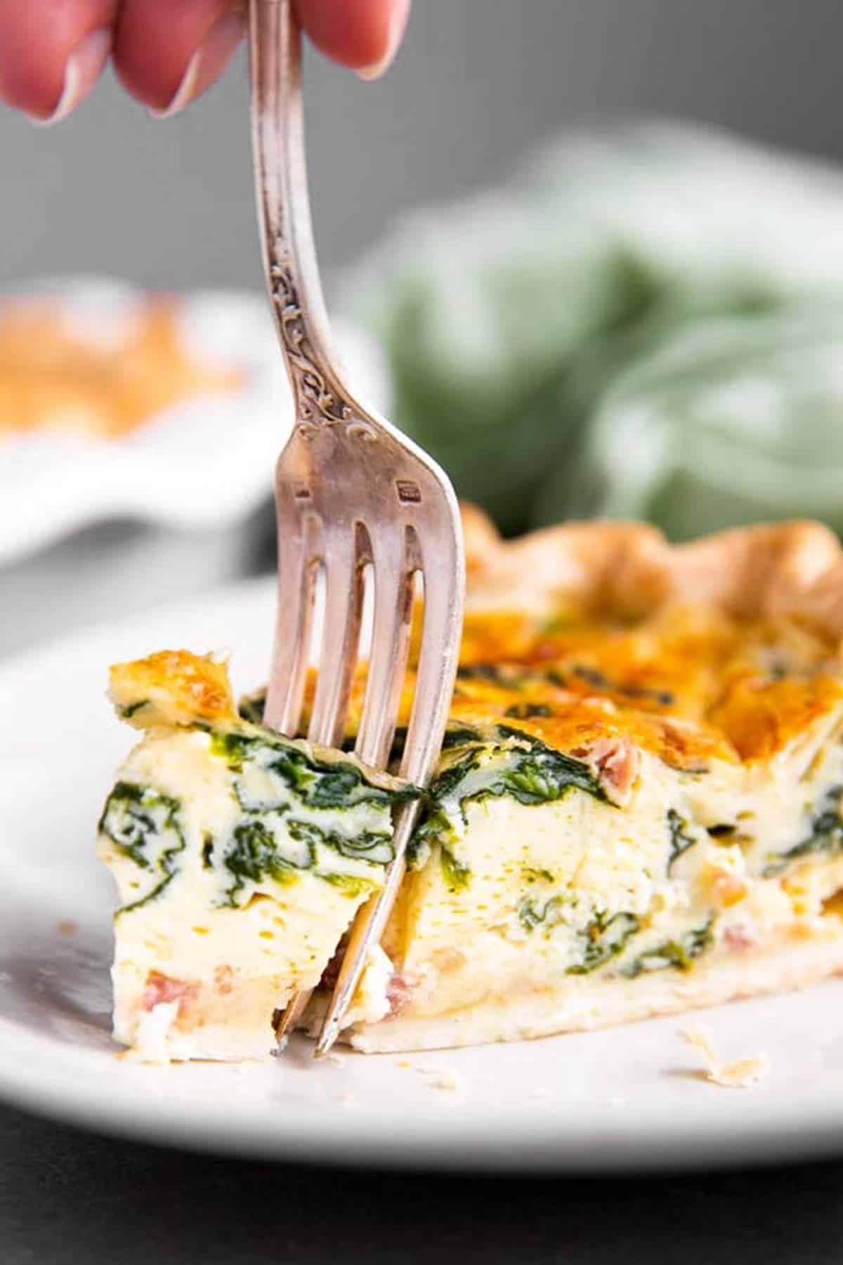 fork in slice of spinach bacon quiche