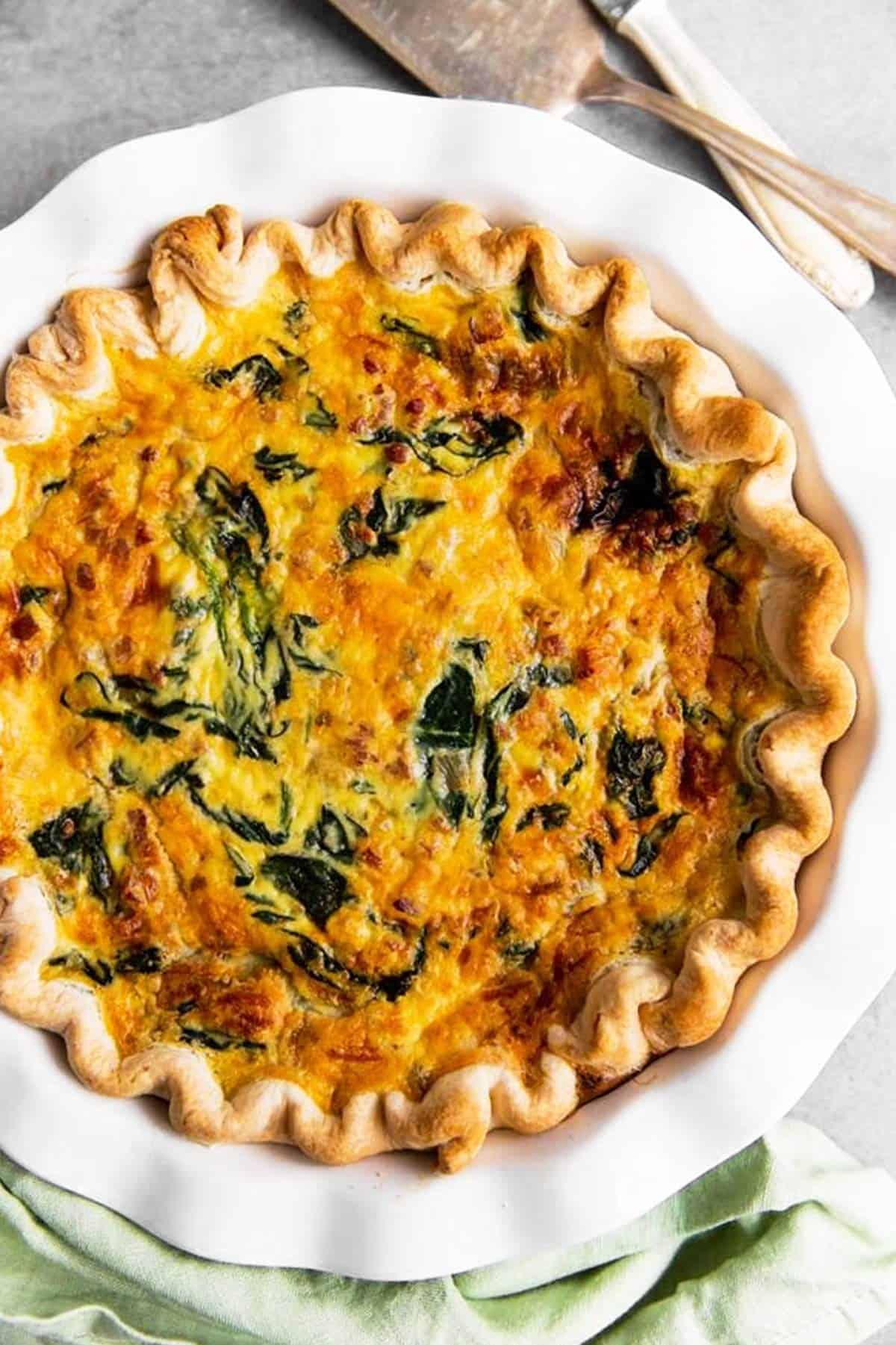 overhead view of baked spinach bacon quiche in white pie plate