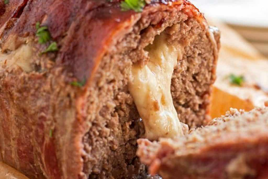 close up photo of melted mozzarella cheese oozing out of a sliced meatloaf