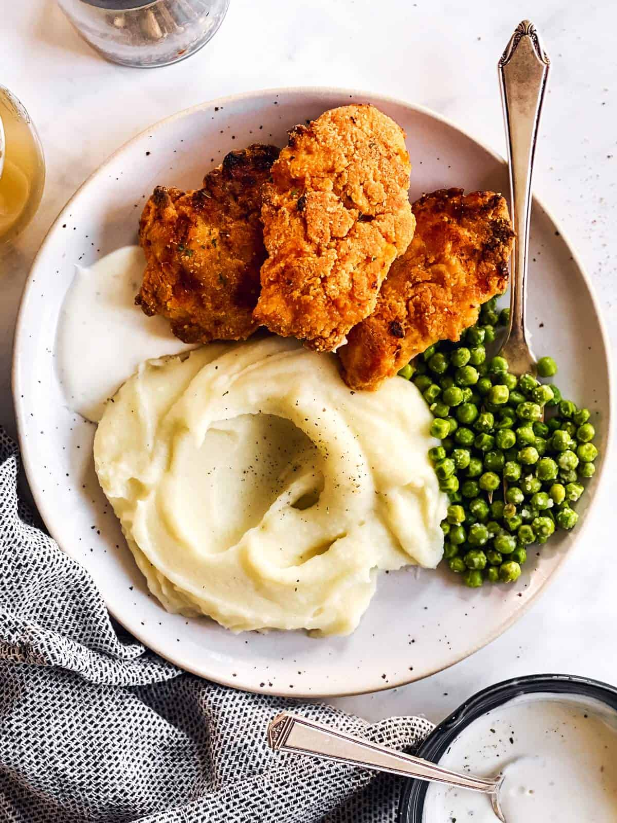 plate with mashed potatoes, peas and fried chicken