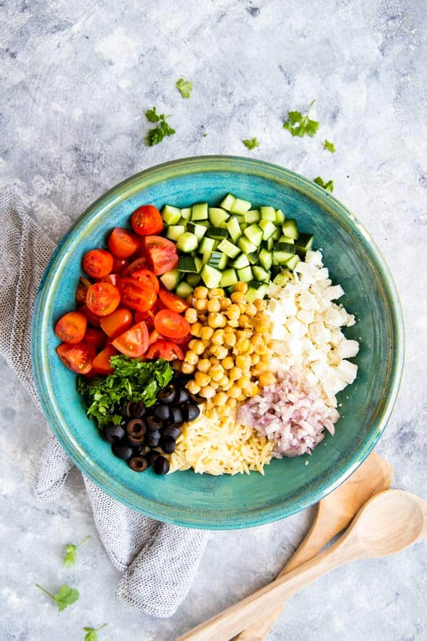 ingredients for greek orzo salad in a large blue bowl