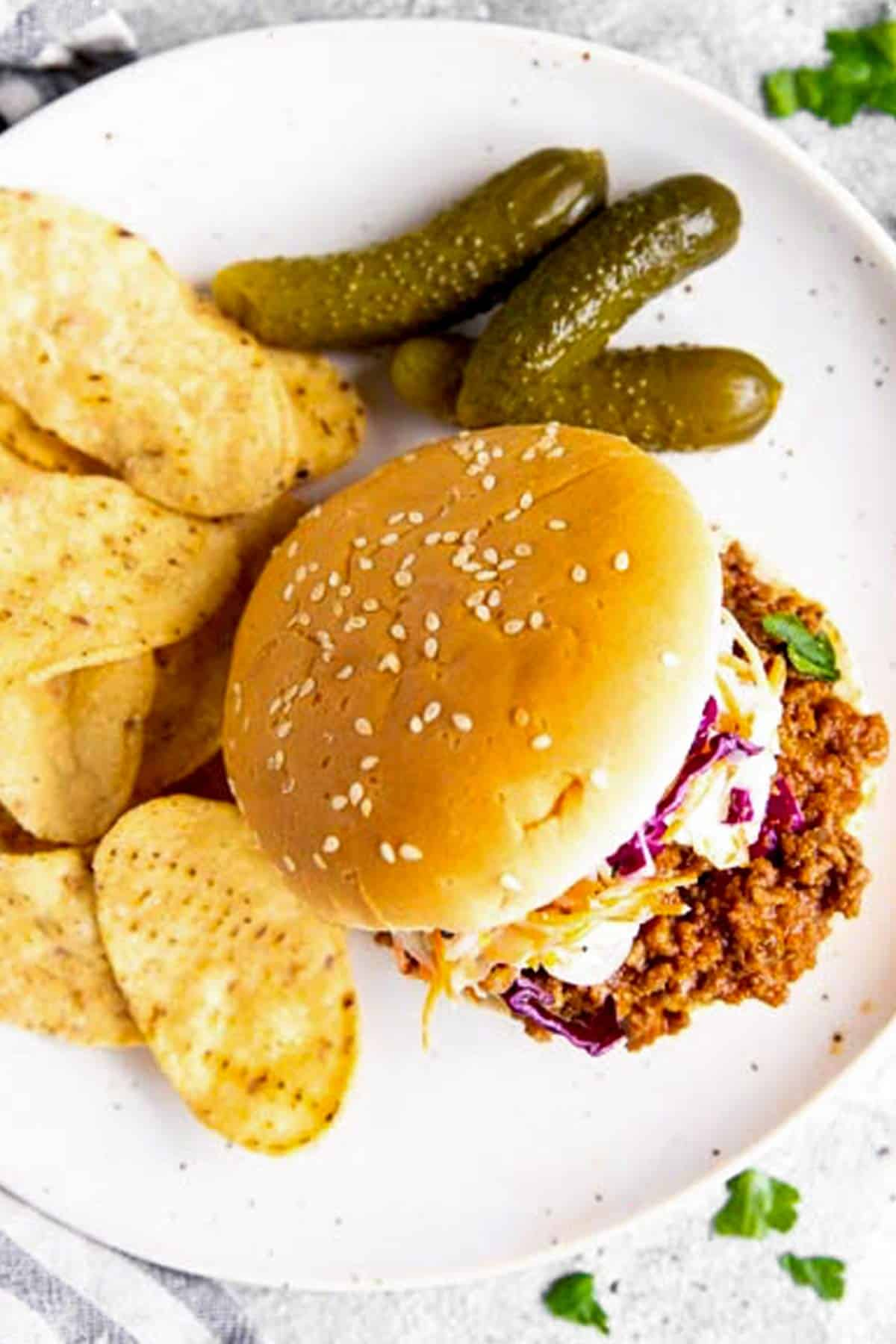 overhead view of sloppy Joe bun with chips and pickles on white plate