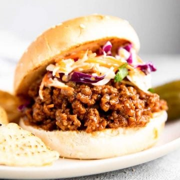 sloppy joes with coleslaw on a white plate