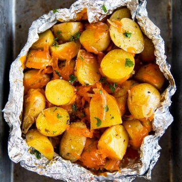 metal baking pan with a foil pouch of campfire potatoes