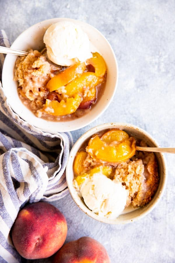two white bowls with peach cobbler and vanilla ice cream