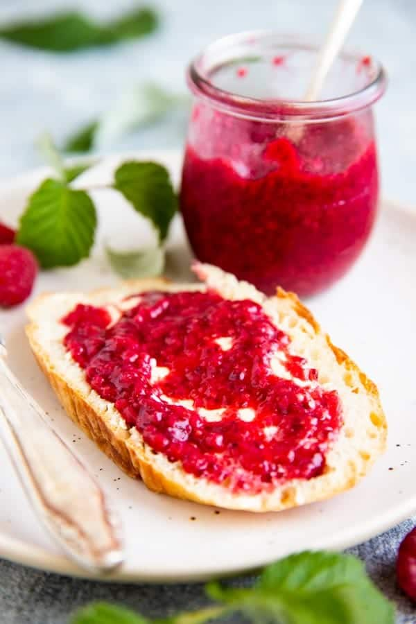 slice of no knead bread with homemade raspberry jam on a plate