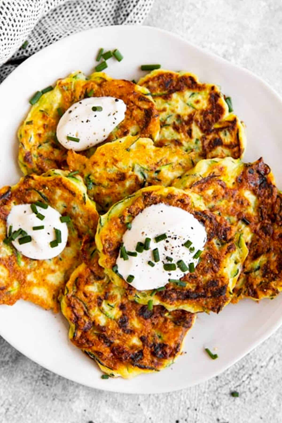 overhead view of zucchini fritters on white plate