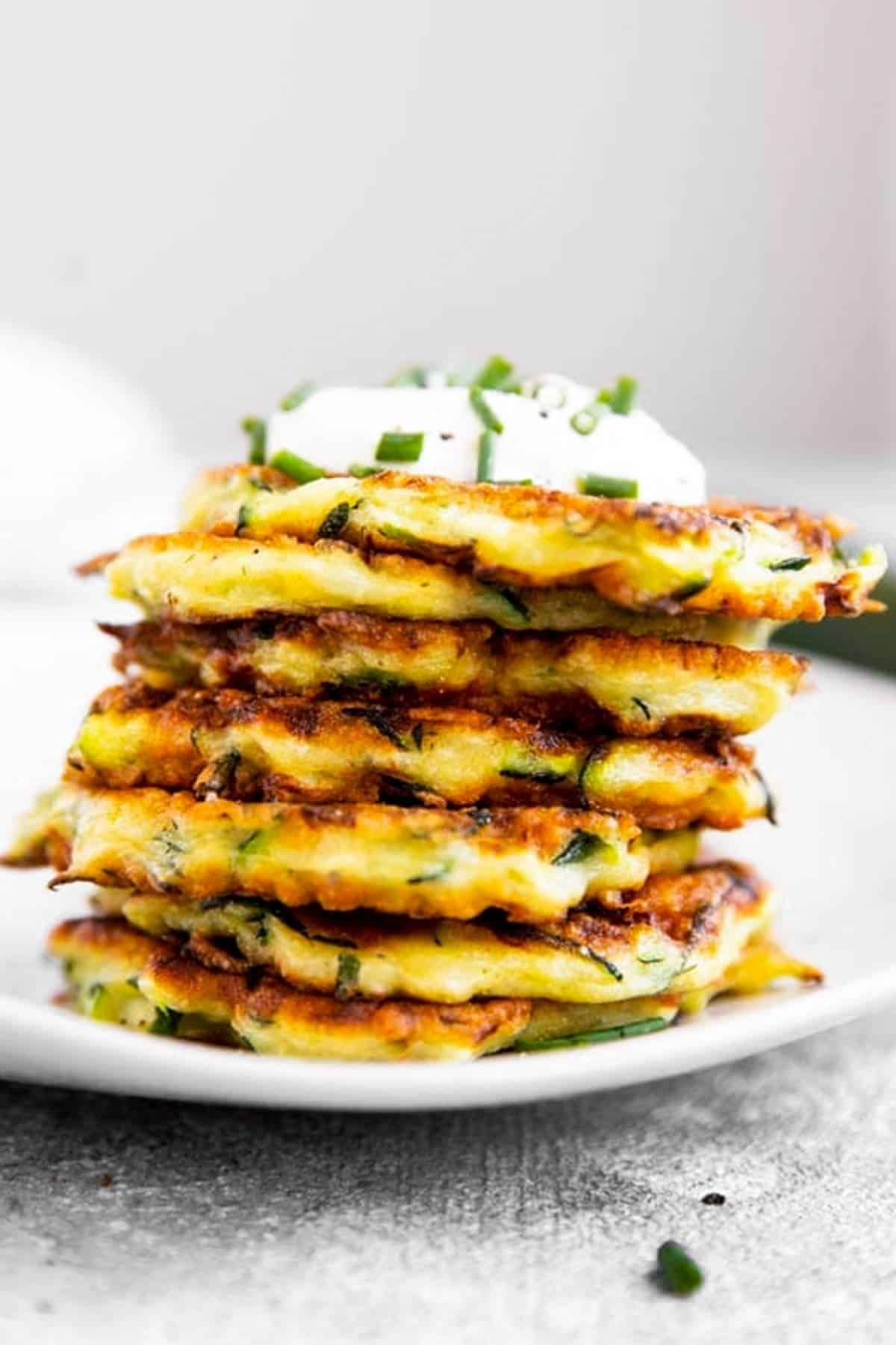 stack of zucchini fritters on white plate
