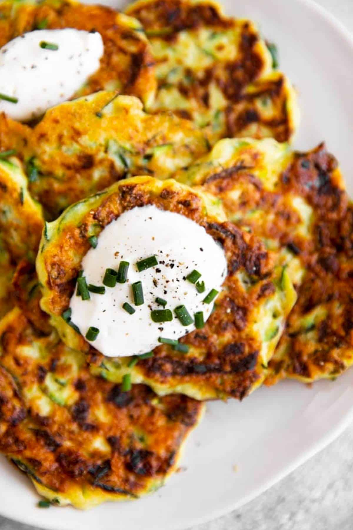 close up photo of zucchini fritters on plate with sour cream