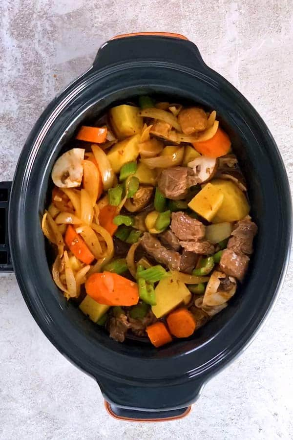 uncooked beef stew in a slow cooker