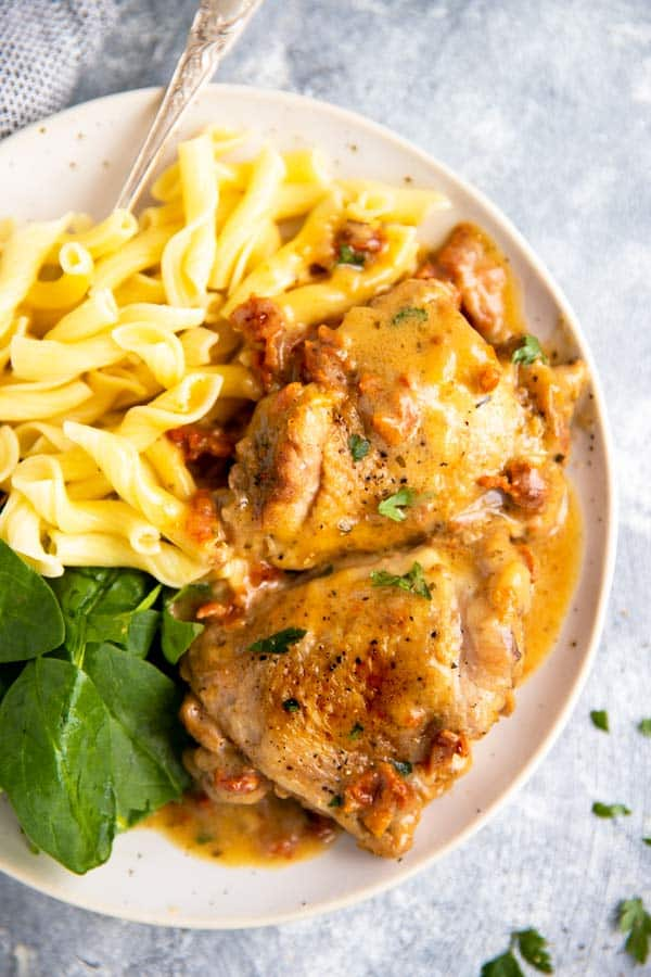 plate with instant pot chicken thighs, pasta and baby spinach